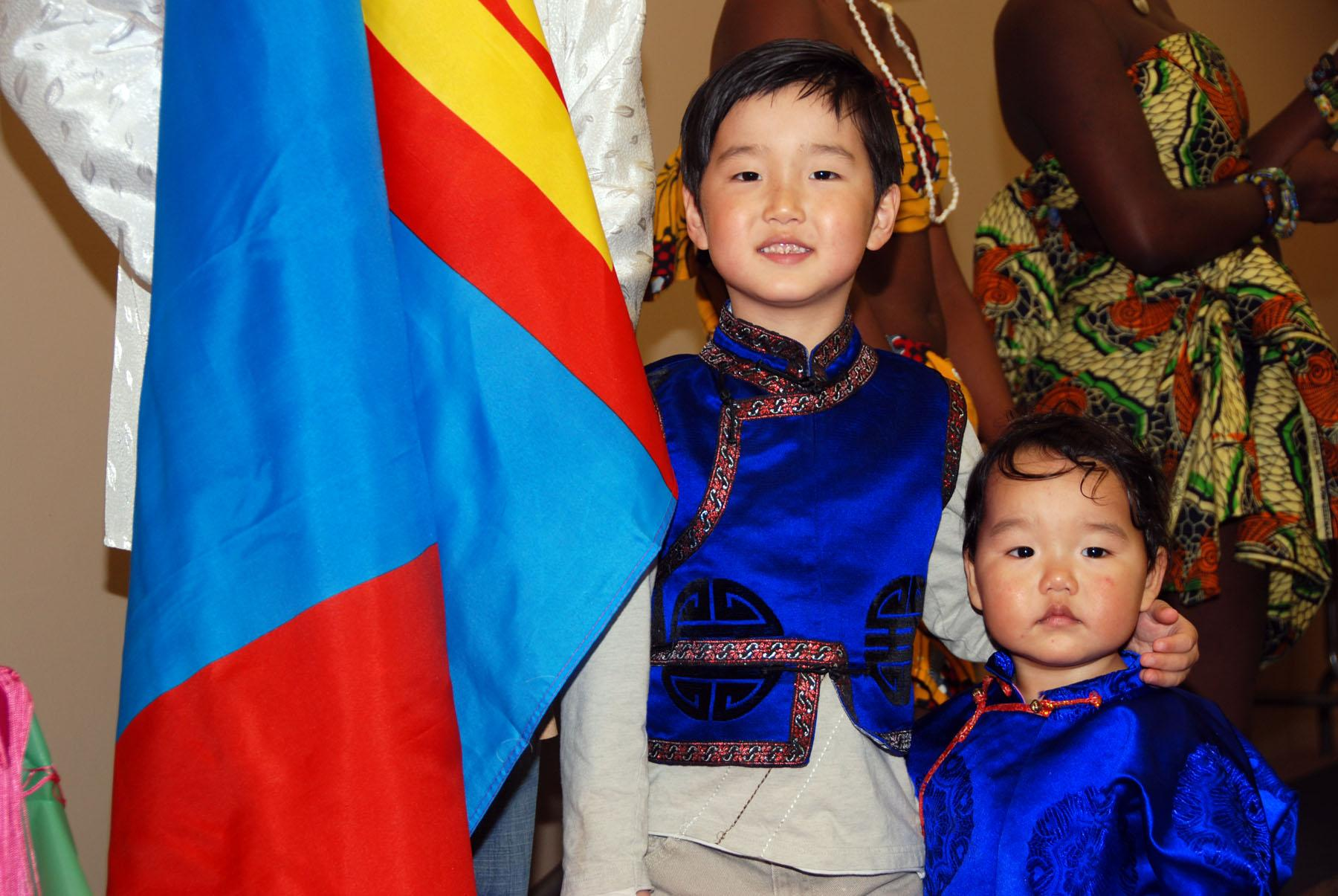 Irmuun Tsogbayar (right) and Ireedui Tsogbayar (left) stand next to their father as he holds the flag of Mongolia during a parade of flags at the 10th annual Northeast Community College Culture Show Sunday night.Tsogbayar Tsendbaatar is one of 41 international students from 17 countries attending Northeast this year.