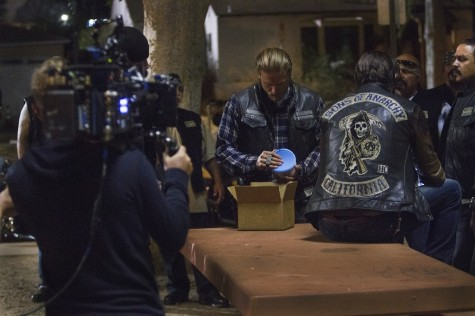 Sons of Anarchy star Charlie Hunnam opens a container that was delivered by Moses (Mathew St. Patrick) during a taping on location in North Hollywood Aug. 15, 2014 in Los Angeles.