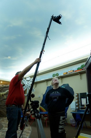 Instructor Timothy Miller and Digital Cinema student Madison Hill use a camera crane to follow a miniature train in the Discovery Children's Zone