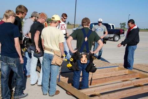 Pulling together for Pilger Ryan Hobza, building construction instructor at Northeast Community College, instructs members of his freshman class as they construct a shed at First Christian Church in Norfolk. The church accepted the help from the students to construct two of the sheds, which will be sent to Pilger along with several others. First Christian is providing the sheds to victims of a June 16 tornado who plan to rebuild their homes in the Stanton County village. (Courtesy Northeast Community College)