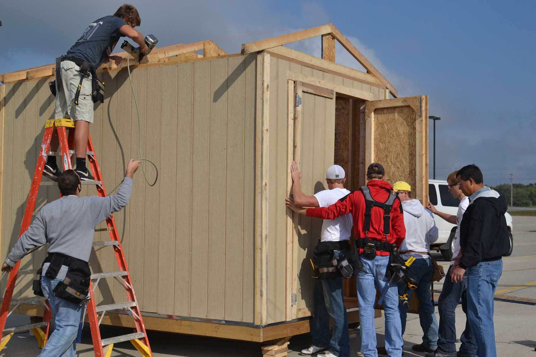 Ryan Hobza (right), building construction instructor at Northeast Community College, oversees members of his freshman class as they construct a shed at First Christian Church in Norfolk. The church accepted the help from the students to construct two of the sheds, which will be sent to Pilger along with several others. First Christian is providing the sheds to victims of a June 16 tornado who plan to rebuild their homes in the Stanton County village. (Courtesy First Christian Church)