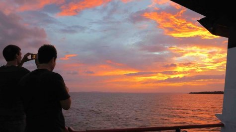 Tourists on a ferry headed to Ometepe Island in Lake Nicaragua snap photos of a spectacular sunset on August 12, 2014. The island, dominated by two volcanoes, is growing as a tourist destination.