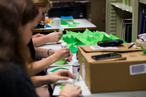 Northeast theatre staff making leaves with tissue paper, wire, and twigs