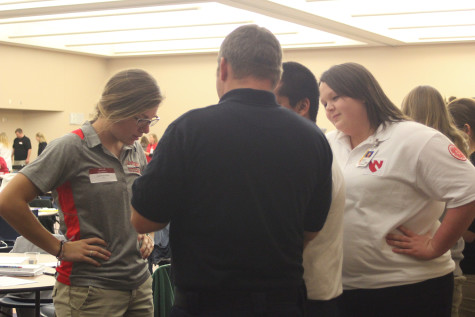 Hannah Burbach (r), pre-nursing UNMC junior consults with her team