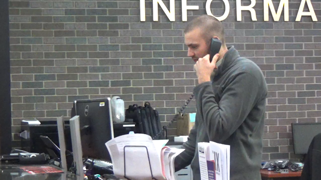 Service Center Supervisor Alex Cook takes a phone call at the Northeast Help Desk