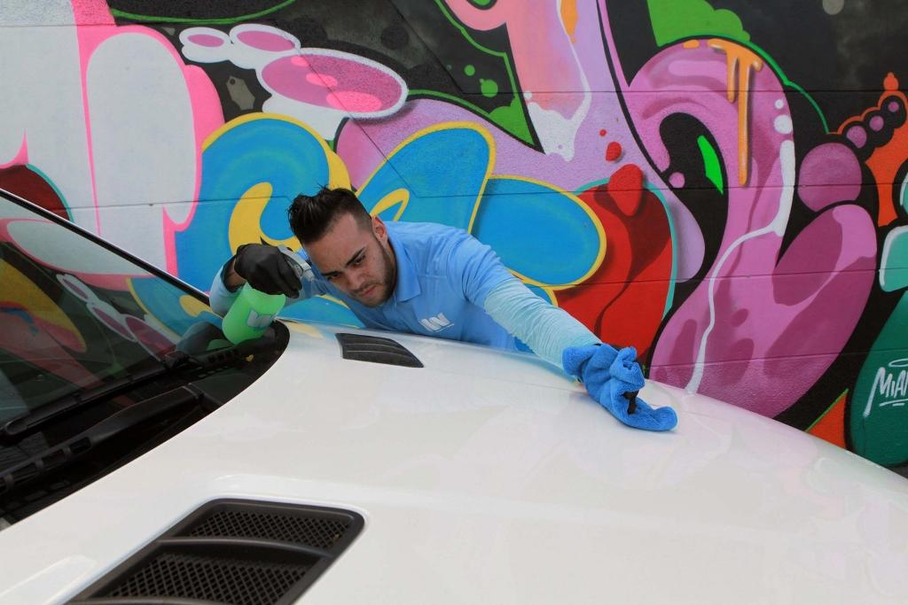 Fidel Miranda, hiring manager of WashMyWhip, works on a car at WashMyWhip in Wynwood, Fla. WashMyWhip is an on-demand, eco-friendly car-care service. (Roberto Koltun/Miami Herald/TNS)