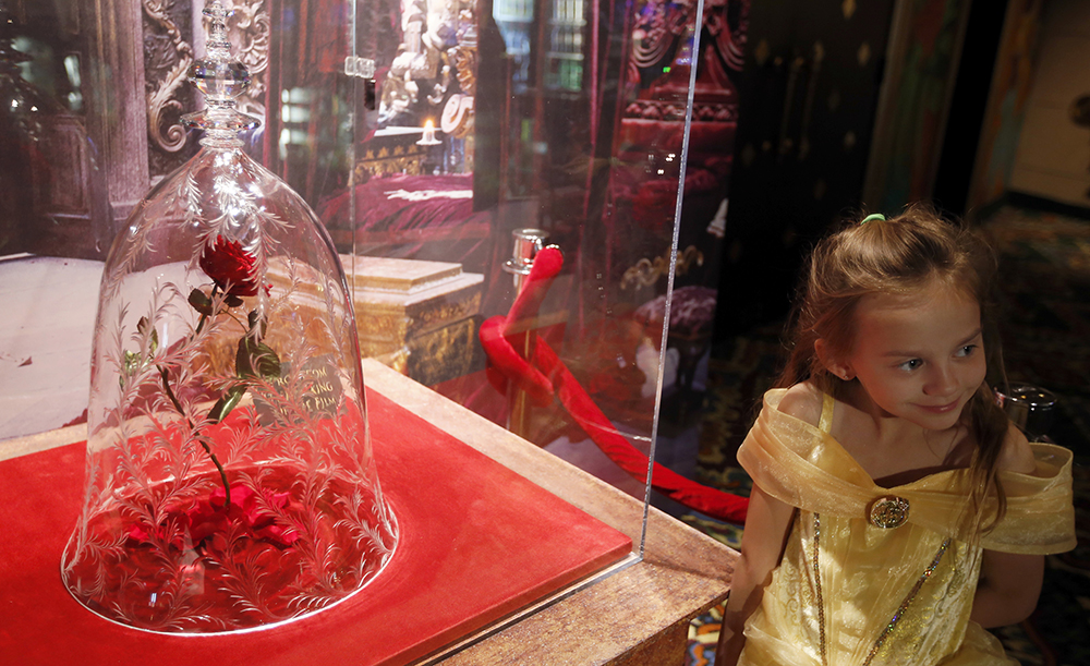 Rillie Duce, 6, poses with the rose in the lobby during the Beauty and the Beast Los Angeles premiere at the El Capitan Theatre March 16, 2017 in Hollywood, Calif.  (Francine Orr/Los Angeles Times/TNS)