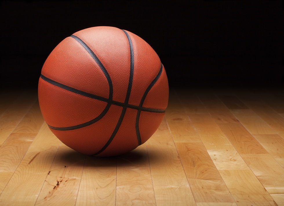 A basketball with a dark background on a hardwood gym floor
