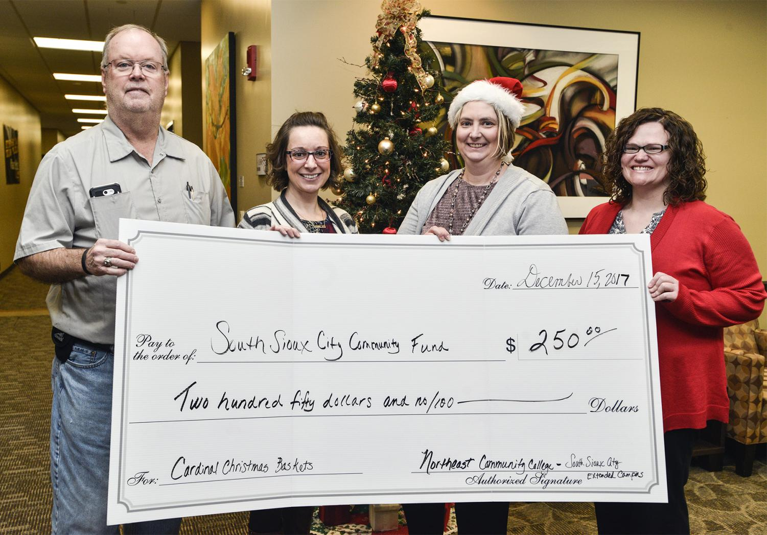 Bill Garvey Sr., co-chair of the Cardinal Christmas Baskets program, accepts a check for $250 from Northeast Community College representatives Kristina Coombs, service center specialist (left), Dr. Cyndi Hanson, executive director, and Cara Watchorn, student support specialist. The funds were raised by allowing Northeast employees to pay to wear jeans on certain Fridays throughout the past year.