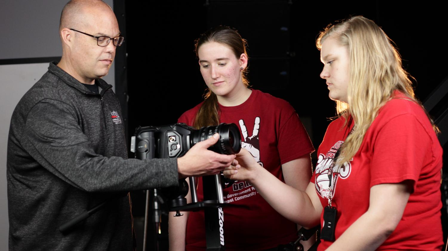 Brian Anderson, media arts - broadcasting instructor at Northeast Community College, explains camera and lens setting techniques to Emma Meisenheimer, Hartington, (center) and Madison Siedschlag, Pierce, students in the College's Media Arts program. (Courtesy Northeast Community College)